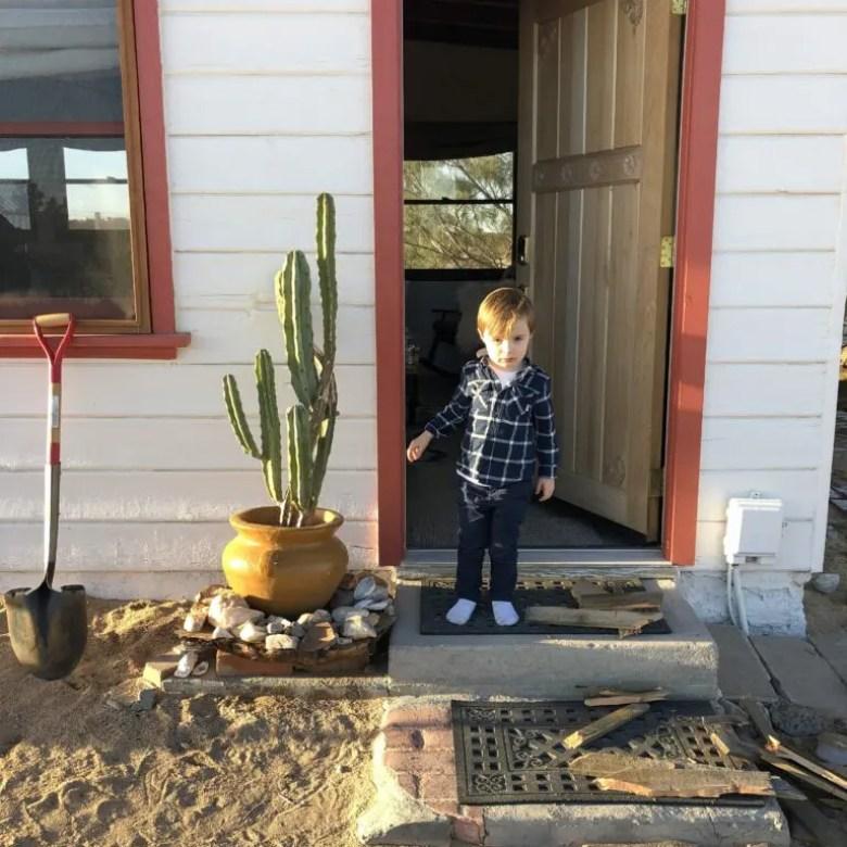 Enfant dans embrasure de la porte d'une maison dans le désert