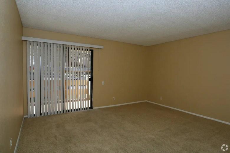 Pièce vide d'un appartement avec stores ouverts et moquette au sol