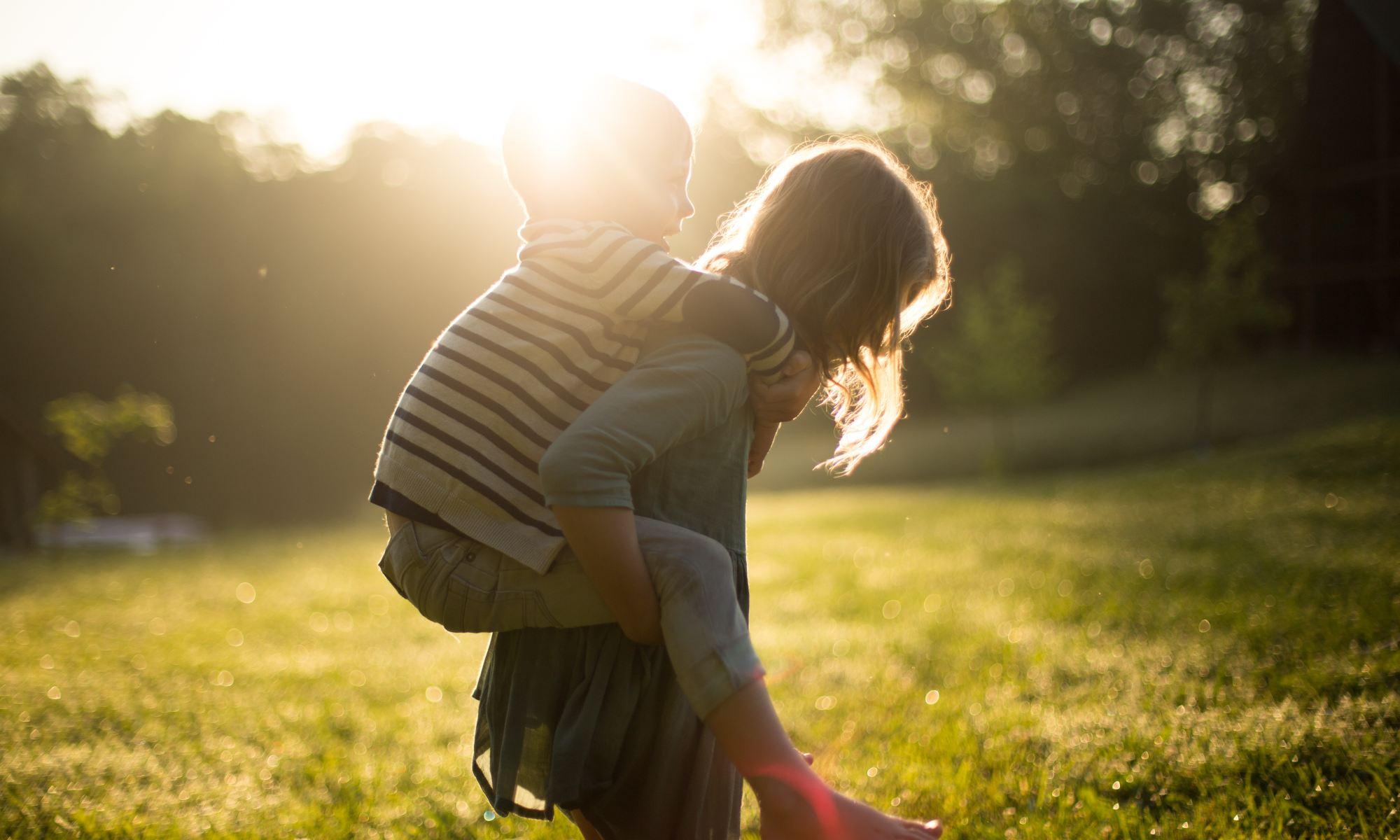 Un garçon sur le dos d'une fille dans le soleil couchant