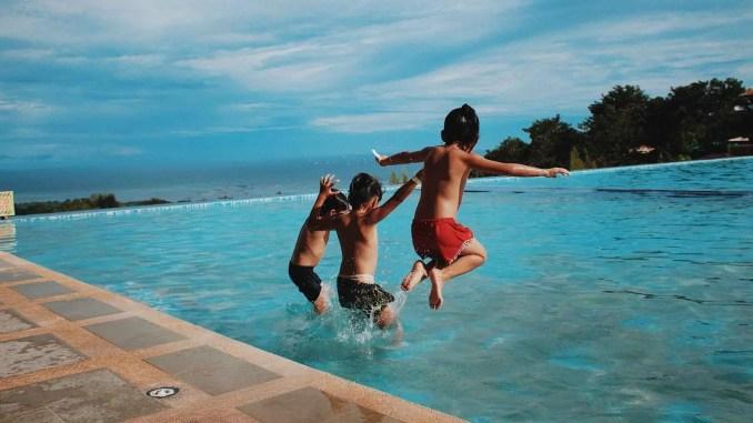 enfants sautant dans une piscine