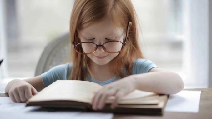 - girl in blue short sleeve t shirt reading book