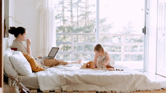 - woman-using-laptop-while-daughter-playing-with-constructor-3975644