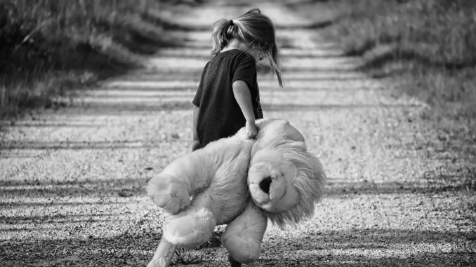 - photographie en niveaux de gris d une fille tenant un jouet en peluche