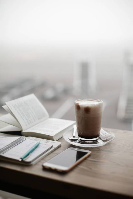 a glass of iced coffee next to an open book and open notebook