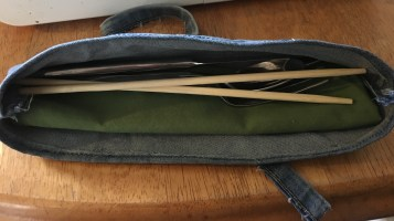 A denim cutlery case holding a green cloth napkin, silverware and wooden chopsticks. Handcrafted by Second Time Around Homestead.