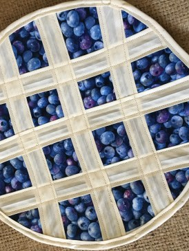 A handsewn hot-mat crafted to look like a blueberry pie. Handcrafted by Second Time Around Homestead.