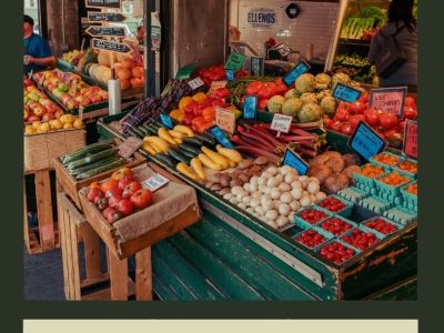 Picture of a stall filled with fresh fruit and vegetables at an outdoor market.