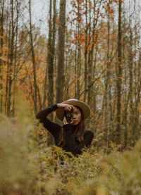 stylish young asian female photographer shooting autumn forest on vintage camera