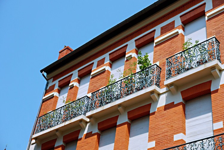 Ocre building with white blinds and balcony - Visit Occitanie