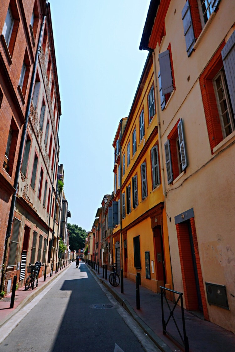 Street with pink coloured houses - Visit Occitanie