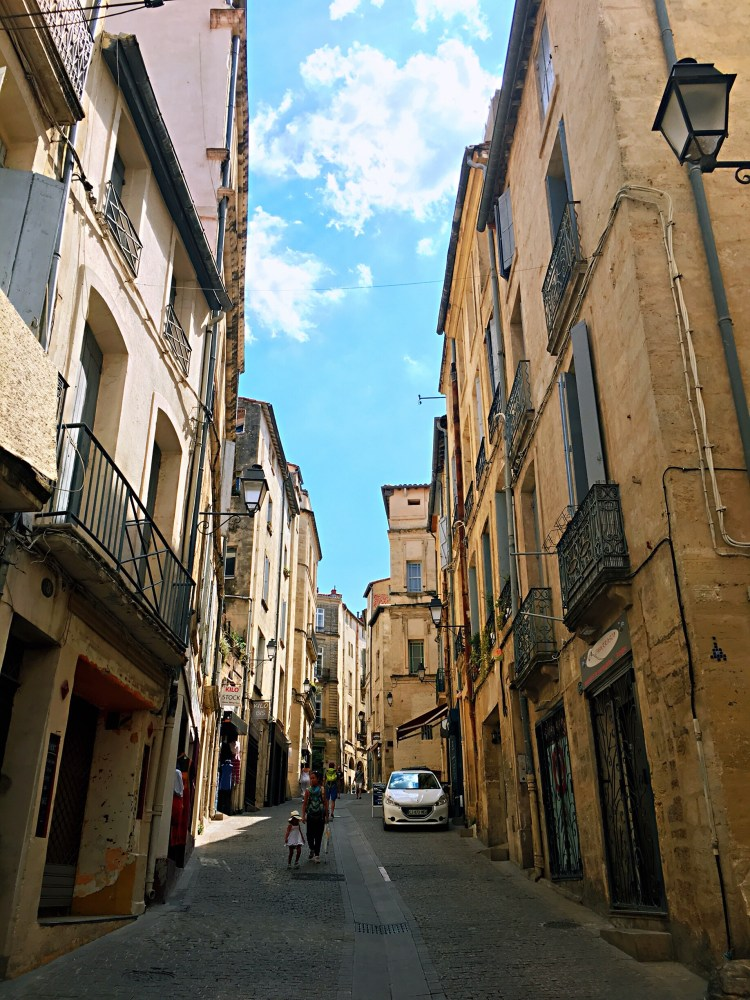 Woman walking with a little girl in charming street of Montpellier - Visit Occitanie
