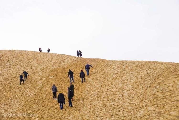 People climbing the steep Dune du Pilat
