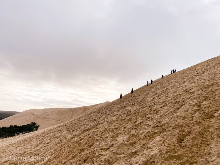 Line of people climbing the steep Dune du Pilat, dark clouds