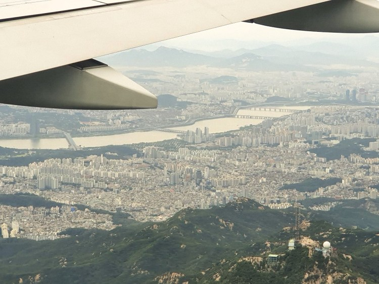View of plane wing flying over Busan, South Korea