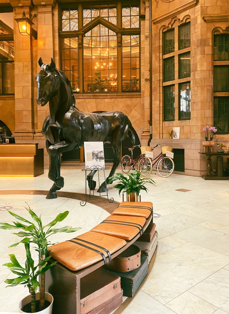 The lobby of Kimpton Clocktower Hotel with a black horse and two vintage bikes
