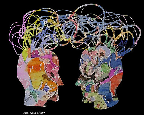 "A watercolor illustration showing two profile heads with a jumble of ""wires"" connecting them."