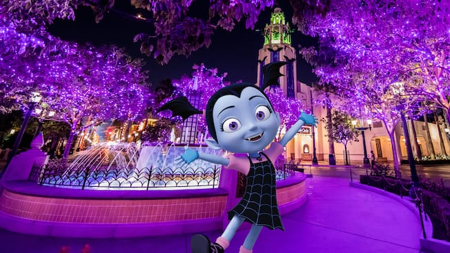 Surrounded by spooky décor, Disney Junior's Vampirina stands outside the theater in Disney California Adventure Park
