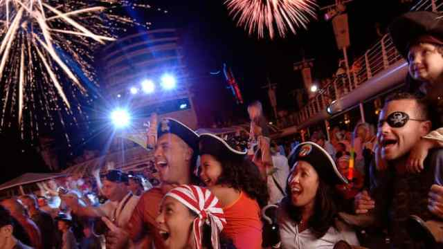 Throngs of people, many dressed in pirate attire, enjoy a fireworks display on the deck of a cruise ship