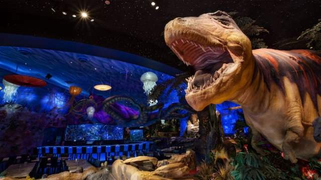 A 15-foot T-Rex shows its sharp teeth and a giant octopus lurks in the background