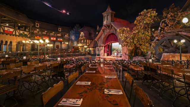 Long communal dining tables across from a stage in Biergarten Restaurant in Germany Pavilion at Epcot