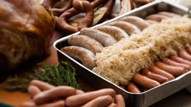 Pan filled with sauerkraut and 2 types of German sausages sitting on a table next to meats and pretzels