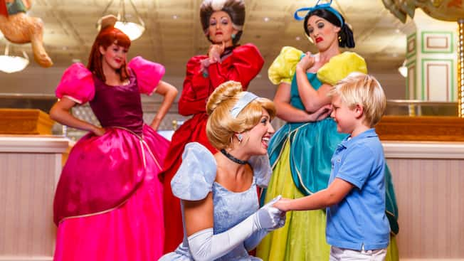 Cinderella welcomes a boy while her evil stepmother and 2 sisters look in disgust.