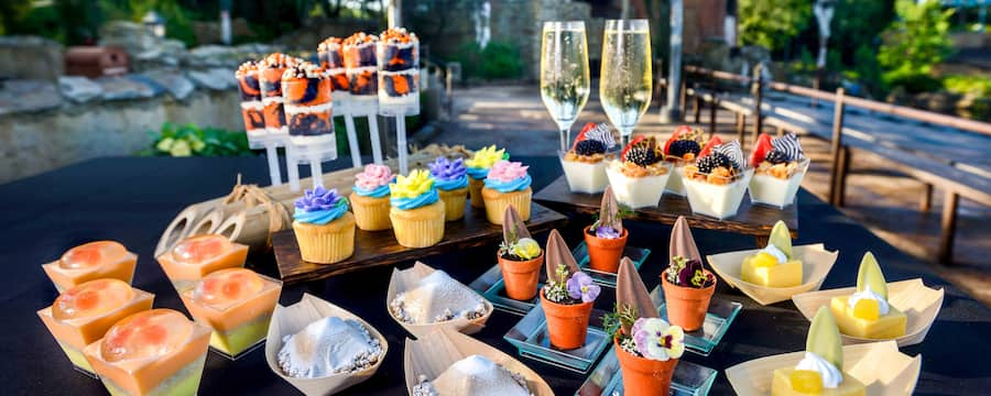 A table set with various desserts and 2 glasses of champagne