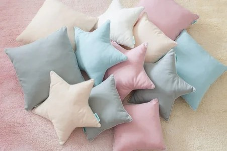 a selection of star-shaped and square cushions in pinks, creams and blues