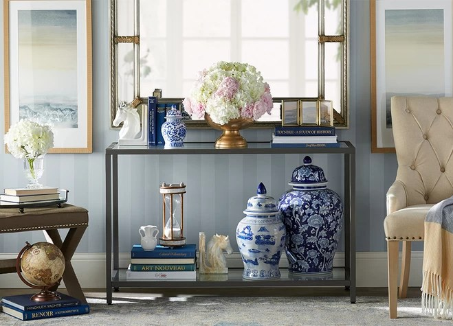 a classic blue and white palette leather bound titles and antique inspired accents like a pair of porcelain urns and equine bookends bring a sense of