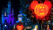 Halloween-themed lanterns shaped like Mickey Mouse on display directly in front of Cinderella Castle