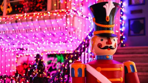 Close-up of a toy soldier with sparkling holiday lights in the background