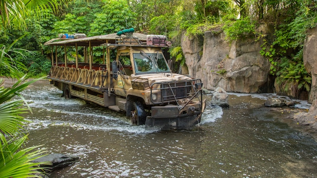 An open-air safari bus drives in a shallow river in the African outback