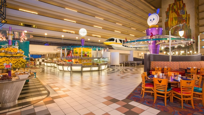 Chef Mickey's as seen from the edge of the dining area, with a monorail whizzing by