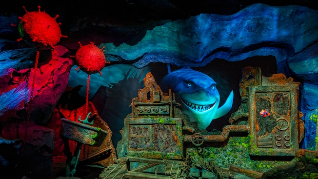 An underwater scene from Disney•Pixar's 'Finding Nemo' with rusting human items and Bruce the shark