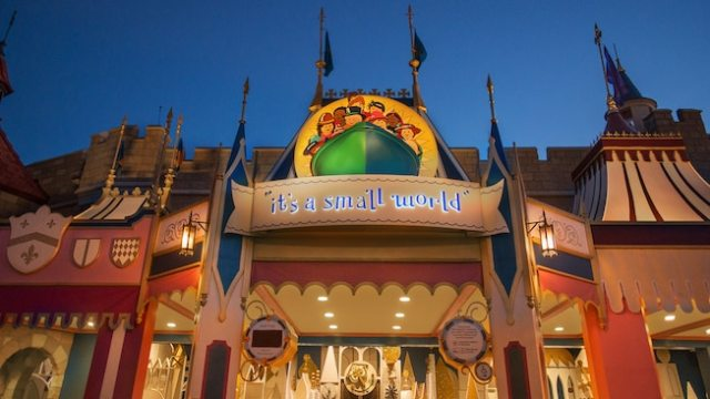 "Nighttime view of the gold fantastical entrance to ""it's a small world"""