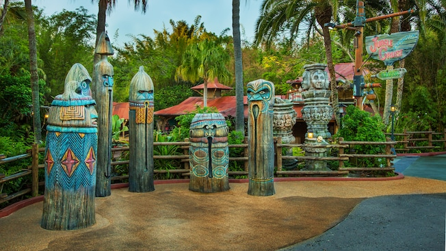 Colorfully painted tiki totems and sign stand on a patio outside the Jungle Cruise