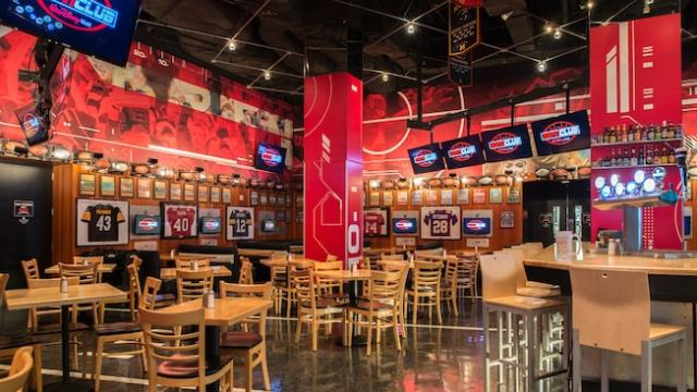 The interior of the espn club featuring flat screen televisions, tables, chairs, framed jerseys, beer and more
