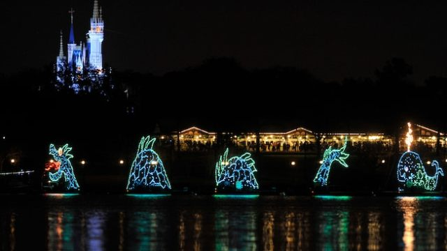 A sea serpent float in the Electrical Water Pageant and Cinderella Castle in the background