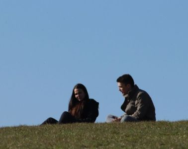 woman and man sitting on a hill together talking