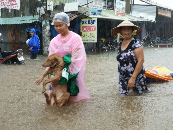 A woman carries her dog as she evacuates from the flooded area.