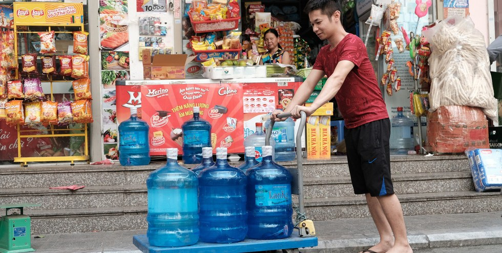 <em>A resident in Hoang Mai District, Hanoi purchases bottled water on October 13, 2019. Photo:</em> Mai Thuong / Tuoi Tre
