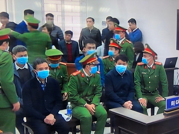 <em>Nguyen Duc Chung (first row, second right) and his accomplices are seen during their trial at the Hanoi People's Court on December 11, 2020. Photo:</em> Nam Tran / Tuoi Tre