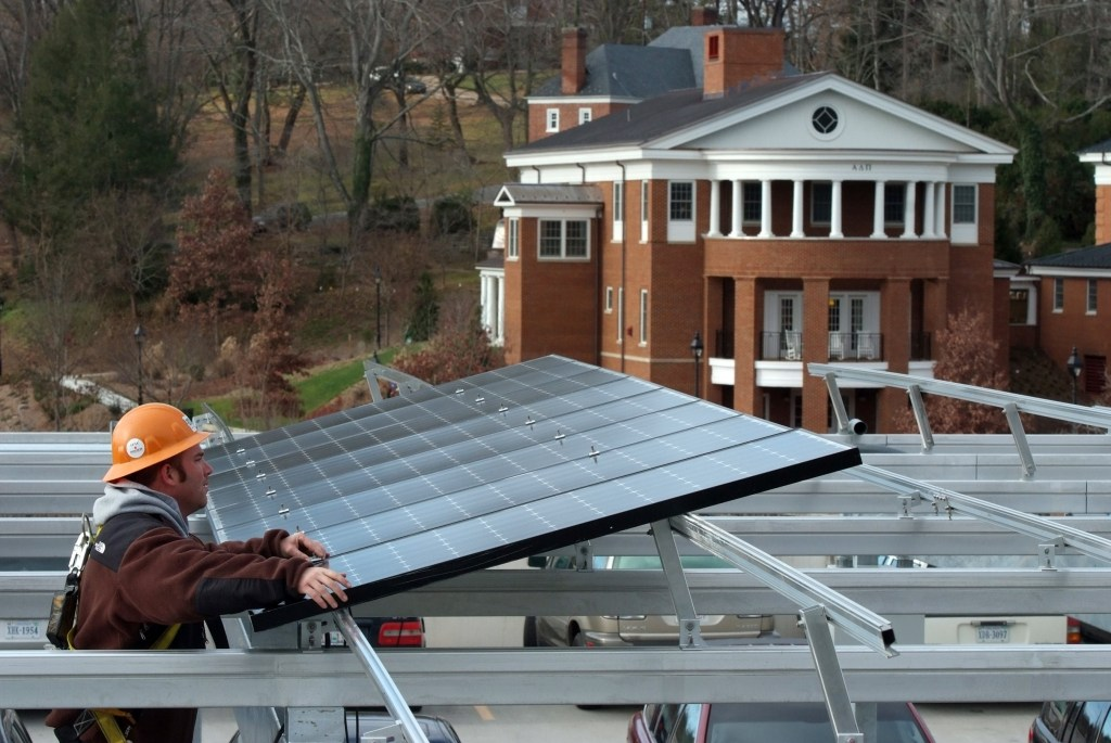 A solar installer places a solar panel on Washington and Lee's parking canopy.