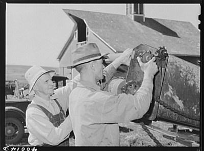 Farmers repairing a tractor.
