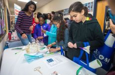 Students build straw rockets at Maker Faire NoVa's tabletop.