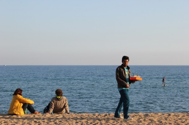 Waiter delivering drinks on Barceloneta Beach in Barcelona, Spain