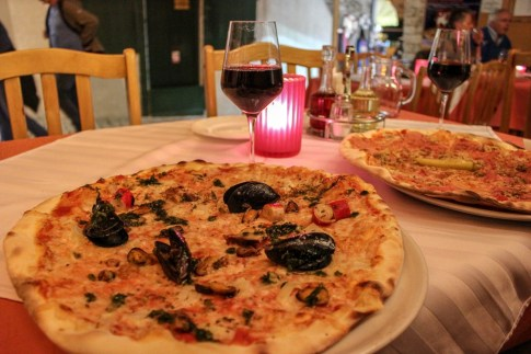 Mixed seafood pizza and glass of wine in Rovinj, Croatia