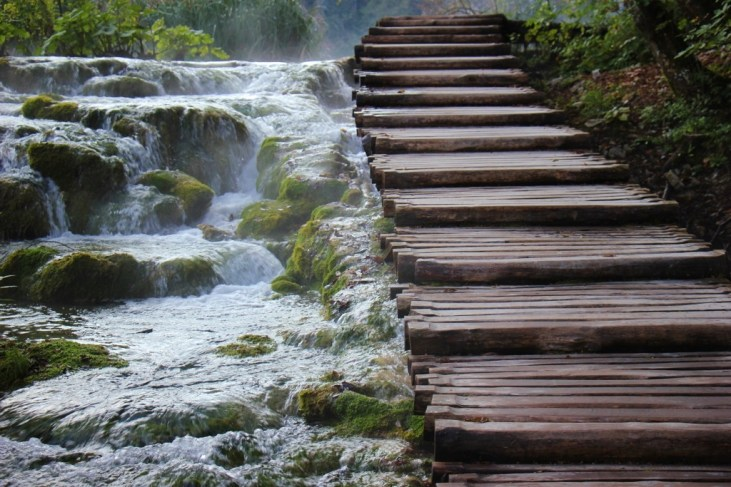 Misty mossy waterfall flows beside stairs, Lower Lakes, Plitvice Lakes National Park, Croatia