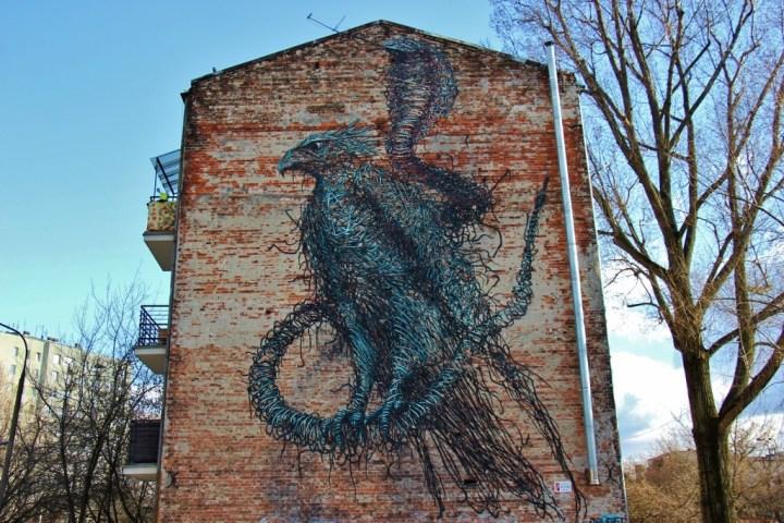 Bird and Snake wall mural street art in Praga neighborhood in Warsaw, Poland