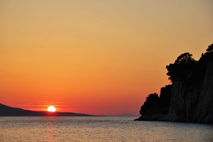 Sun setting behind island in Adriatic Sea, Makarska, Croatia